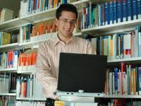Mann mit Notebook vor Bücherregal
