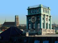 Uhrenturm der TU München vor dem Panorama der Münchner Frauenkirche