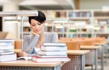 Junge Frau sitzt in der Bibliothek und lernt.