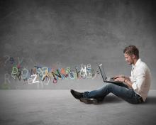 Student mit Laptop am Boden sitzend