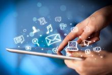 Tablet mit Hand und Social-Media-Piktogrammen